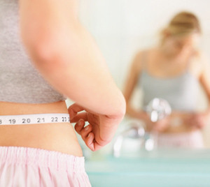 Closeup of a young woman measuring her waist in the bathroom